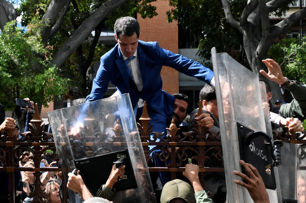 Venezuelan opposition leader and self-proclaimed acting president Juan Guaido is helped to climb a railing in an attempt to reach the National Assembly building in Caracas, on January 5, 2020. - Venezuela's opposition lawmaker Luis Parra -a rival to Juan Guaido- declared himself parliament speaker, as Guaido and fellow opposition lawmakers were blocked from entering the National Assembly. Guaido had been expected to be re-elected parliament speaker but only regime lawmakers and opposition deputies critical of Guaido were allowed to enter the building. (Photo by Federico Parra / AFP)