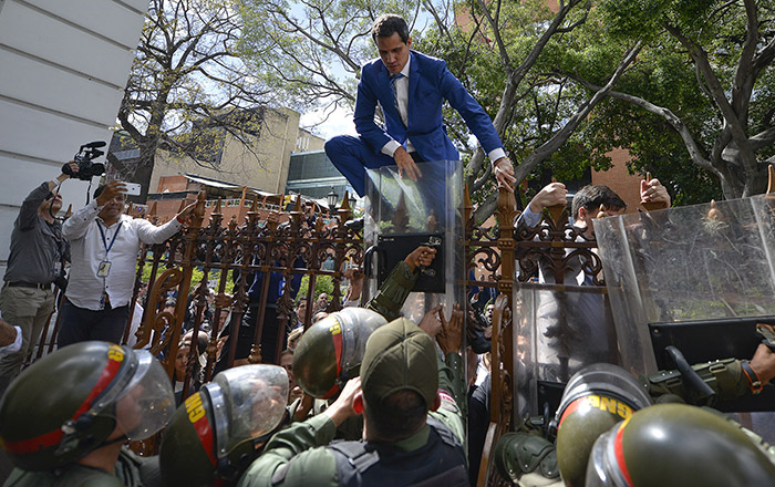 National Assembly President Juan Guaido, Venezuela's opposition leader, climbs the fence in a failed attempt to enter the compound of the Assembly, as he and other opposition lawmakers are blocked from entering a session to elect new Assembly leadership in Caracas, Venezuela, Sunday, Jan. 5, 2020. With Guaido stuck outside, a rival slate headed by lawmaker Luis Parra swore themselves in as leaders of the single-chamber legislature.(AP Photo/Matias Delacroix)